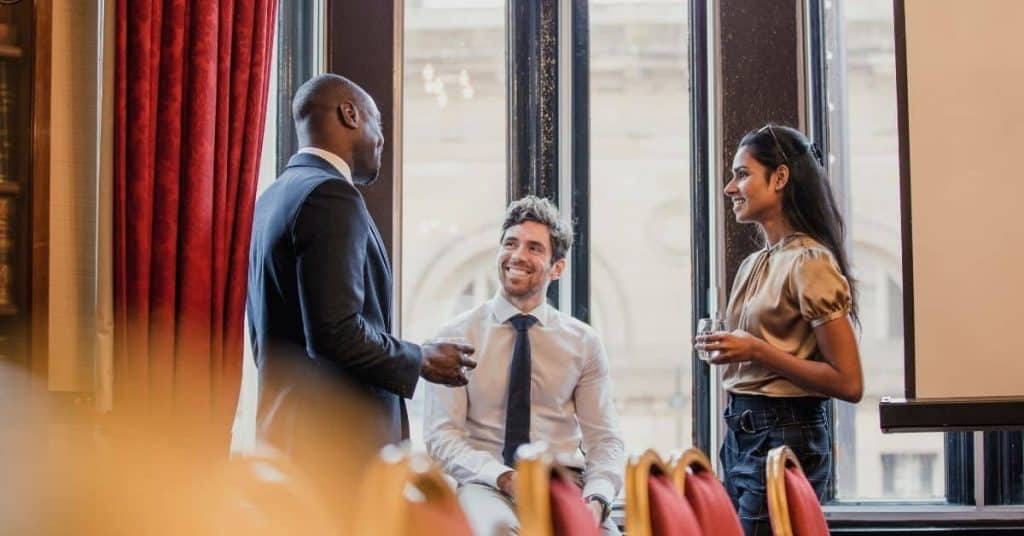 A group of two men and a woman networking in an office. Networking can help you get noticed by hiring managers